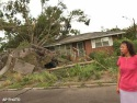 Thu., Aug. 12: Nicci Watson stands in front of her Jacksonville, Fla., home after a tornado, spawned by Tropical Storm Bonnie, uprooted the tree in her front yard.