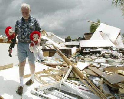 Punta Gorda resident Jack Aurelia of the Windmill Village mobile home park, carries out two dolls that belong to his wife, Aurelia in Punta Gorda, Florida on August 14, 2004. Jack Aurelia mobile home in the background was destroyed when Hurricane Charley passed over Friday afternoon leaving destruction and power outages. REUTERS/Charles W. Luzier