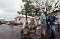 Tommy Arch (R), Larry Maple and Alex Cuesta (L) clear a drain to help reduce flooding in their trailer park after Hurricane Jeanne hit Fort Pierce, Florida, September 26, 2004. Hurricane Jeanne, currently a category three storm is the fourth named storm to approach Florida and the second such storm to attack the treasure coast in a little over a month. REUTERS/Marc Serota