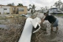 Gustavo Castro clears debris in floodwaters in the Port St. Lucie Mobile Village where he lives in Port St. Lucie, Florida, in the aftermath of Hurricane Jeanne, September 26, 2004. REUTERS/Joe Skipper