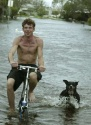 Dan Serales rides his bike with his dog Jewell on the flooded streets of the Barefoot Mobile Home Park in Micco, Florida on September 26, 2004. Hurricane Jeanne made landfall on the East Coast of Florida, three weeks to the day, that Hurricane Fances hit. The fourth to impact Florida in the past six weeks. REUTERS/Charles W. Luzier