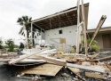 John Dangova of West Palm Beach, Fla., sits among the rubble of the lobby of the Palmwood Motor Lodge in Sebastion, Fla., on Sunday, Sept. 26, 2004. Winds from Hurricane Jeanne blew out the lobby in the middle of the night when it made landfall nearby. (AP Photo/Dave Martin)