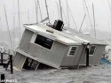 Sun., Sept. 26: A houseboat lies partially submerged as winds and waves continue to batter a yacht basin in Titusville, Fla.